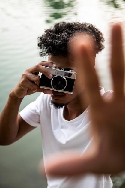 Homem de close-up com câmera tirando fotos Foto Premium