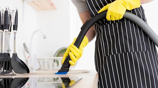 Homem de close-up de limpeza com vácuo Foto gratuita