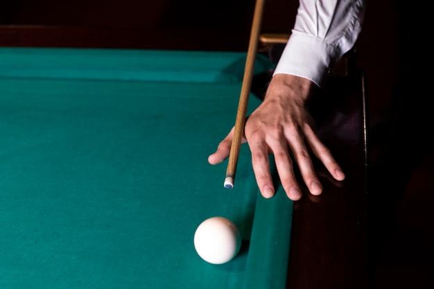 Homem de close-up pronto para bater a bola branca Foto gratuita