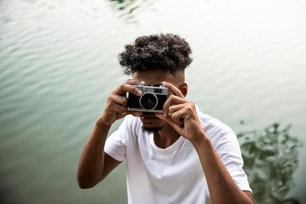 Homem de close-up segurando a câmera Foto gratuita