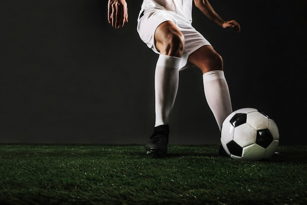 Homem de colheita correndo para chutar a bola Foto gratuita
