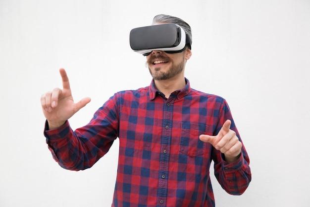 Homem de conteúdo usando fone de ouvido de realidade virtual Foto gratuita