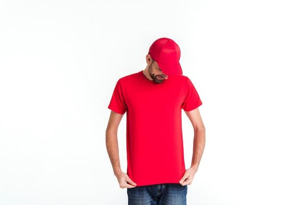 Homem de correio em uniforme vermelho, olhando para baixo Foto gratuita
