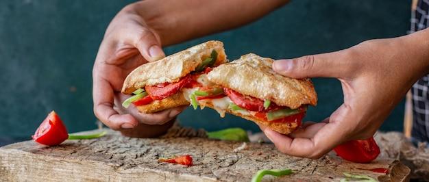 Homem de corte com as mãos sucuk ekmek, sanduíche de salsicha com frango e alimentos misturados Foto gratuita