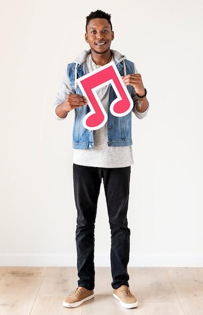 Homem de desentendimento africano segurando um ícone de nota musical Foto Premium