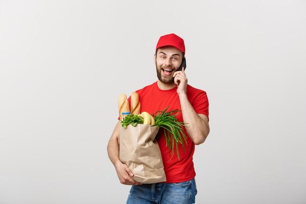 Homem de entrega considerável do mantimento que fala ao móbil e ao saco de papel do mantimento da terra arrendada. Foto Premium