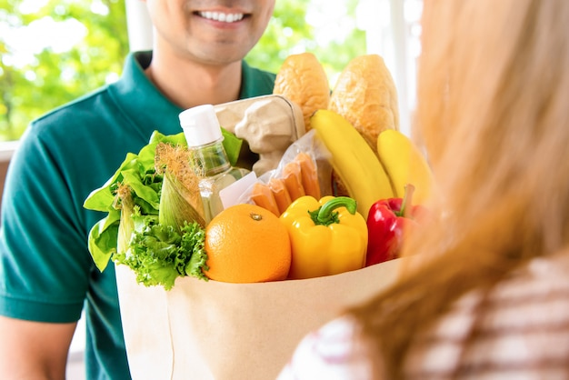 Homem de entrega sorridente dando sacola de compras ao cliente mulher em casa para o conceito de serviço de compras de comida on-line Foto Premium