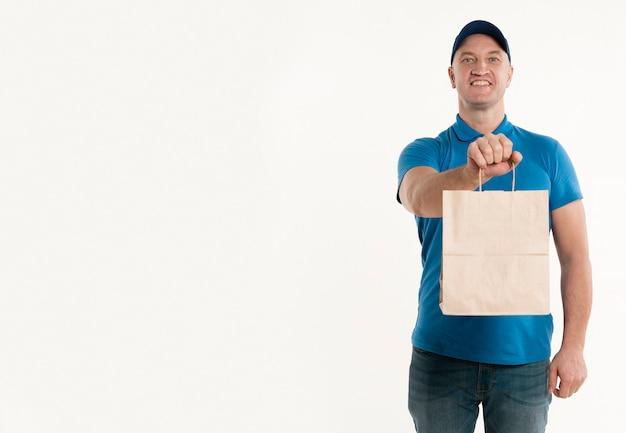 Homem de entrega sorridente segurando o saco de papel com espaço de cópia Foto gratuita