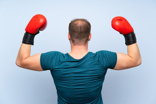Homem de esporte loiro muro azul com luvas de boxe Foto Premium