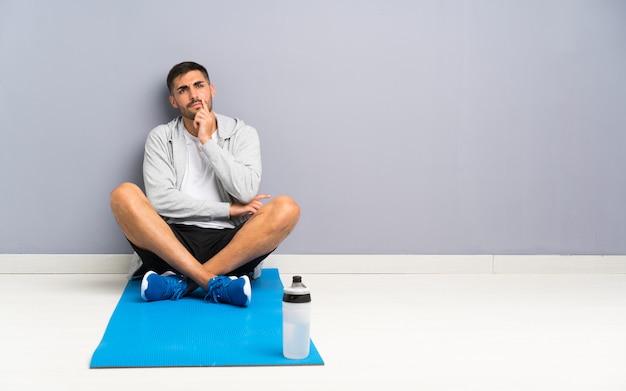 Homem de esporte sentado um no chão pensando em uma idéia Foto Premium