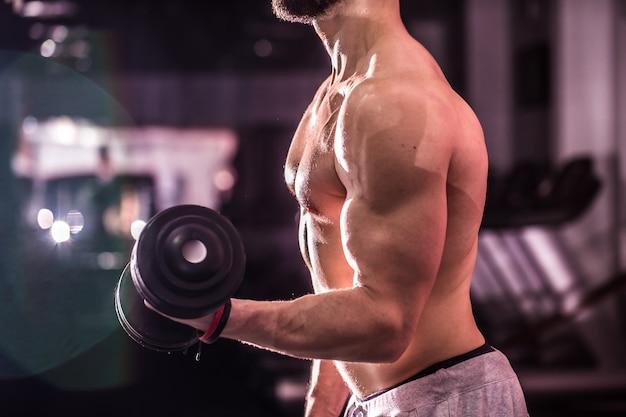 Homem de esportes musculares está envolvido no treinamento de cross fit na academia, o conceito de esporte Foto gratuita