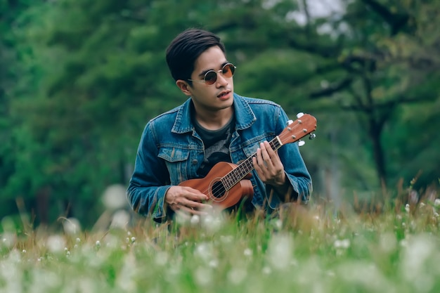 Homem de estilo de vida relaxante no parque com seu tom vintage ukulele Foto Premium