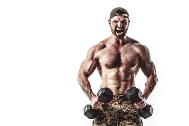 Homem de fisiculturista atleta muscular em calças de camuflagem com um treino de tronco nu com halteres em uma parede branca. Foto Premium