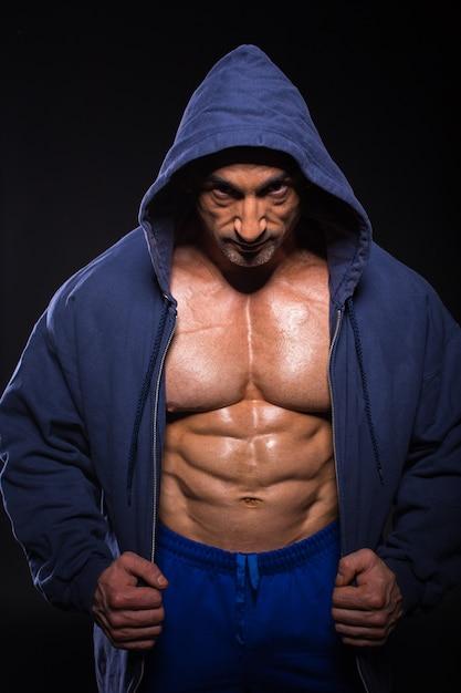 Homem de fisiculturista colocou seu casaco e posando. Foto Premium