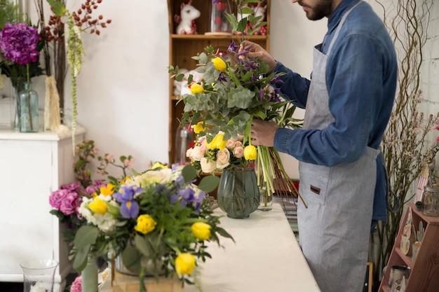 Homem de florista no avental faz um buquê na loja de flores para um presente festivo para um casamento ou aniversário Foto gratuita