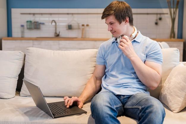 Homem de frente trabalhando em um laptop de casa Foto gratuita