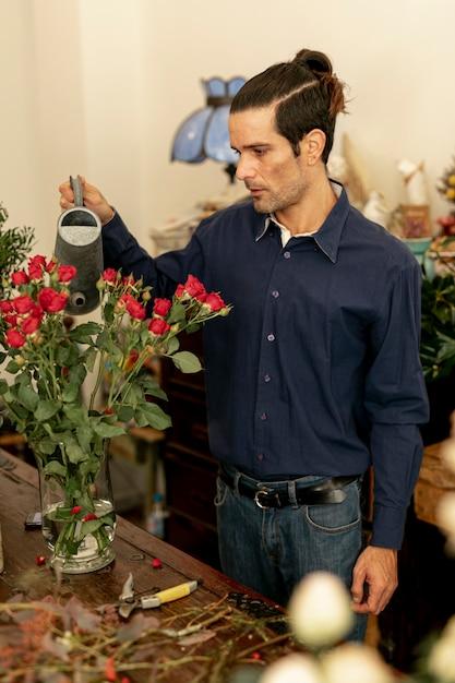 Homem de jardineiro com cabelos longos, regando as plantas Foto gratuita