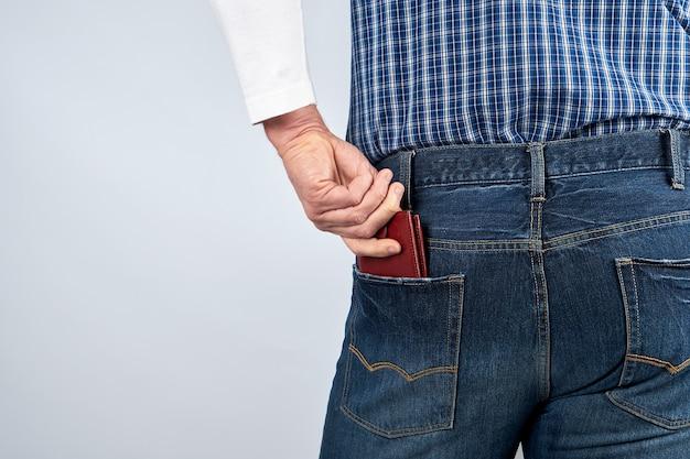Homem de jeans azul e uma camisa xadrez enfia uma carteira marrom de couro no bolso de trás Foto Premium