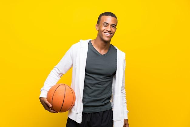 Homem de jogador de basquete americano afro sobre amarelo isolado Foto Premium