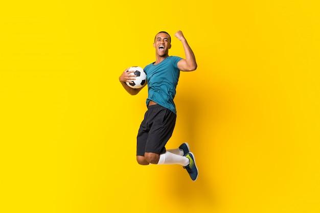 Homem de jogador de futebol afro-americano sobre amarelo isolado Foto Premium