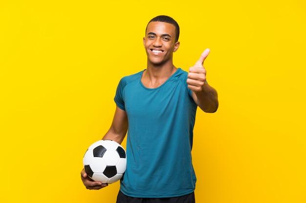 Homem de jogador de futebol americano africano com polegares para cima porque algo de bom aconteceu Foto Premium