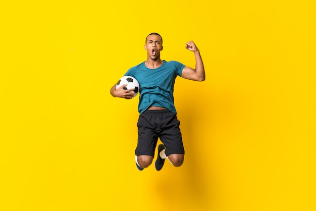 Homem de jogador de futebol americano afro sobre fundo amarelo isolado Foto Premium