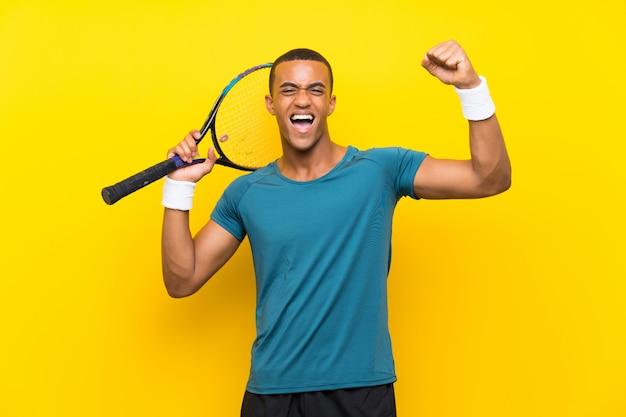 Homem de jogador de tênis americano africano comemorando uma vitória Foto Premium