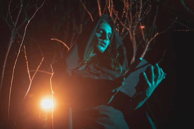 Homem de lado segurando uma lanterna e um livro no meio da noite Foto gratuita