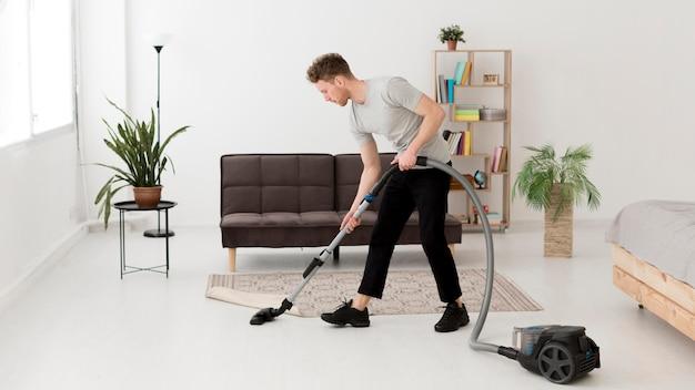 Homem de limpeza com vácuo Foto Premium