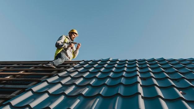 Homem de longo alcance trabalhando no telhado Foto gratuita