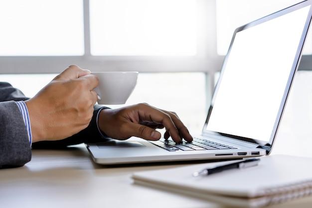 Homem de mão de homem de negócios trabalhando no laptop de tela branca em branco de computador portátil Foto Premium
