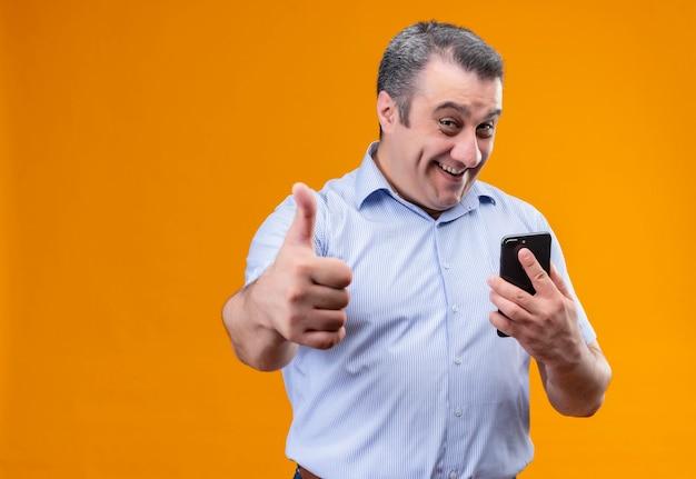 Homem de meia-idade alegre e positivo, vestindo uma camisa azul listrada, segurando um telefone celular e mostrando os polegares para cima Foto gratuita