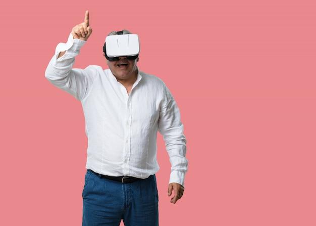 Homem de meia idade animado e entretido, jogando com óculos de realidade virtual, explorando um mundo de fantasia, tentando tocar algo Foto Premium