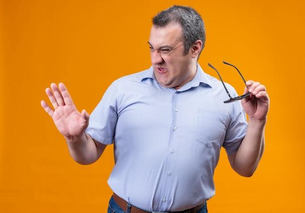 Homem de meia-idade com camisa listrada azul expressando ironia e ódio, mostrando descontentamento segurando óculos escuros sobre um fundo laranja Foto gratuita