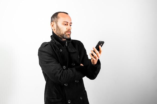 Homem de meia idade com casaco escuta atentamente uma conversa no seu telemóvel Foto Premium