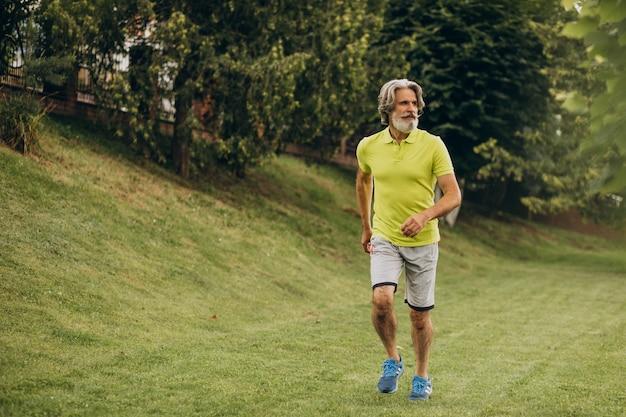 Homem de meia idade correndo no parque Foto gratuita