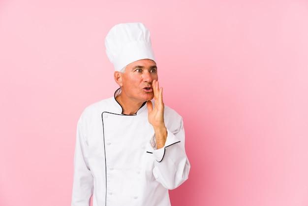 Homem de meia idade cozinheiro isolado está dizendo uma notícia secreta de travagem quente e olhando de lado Foto Premium
