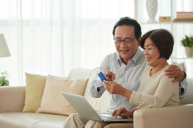 Homem de meia idade e | mulher fazendo compras on-line Foto gratuita