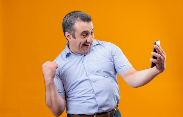 Homem de meia-idade feliz e animado, vestindo uma camisa azul listrada com listras verticais, olhando para o celular e levantando a mão em um gesto de punho cerrado enquanto está de pé sobre uma parte traseira laranja Foto gratuita