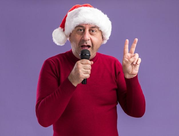 Homem de meia-idade feliz usando chapéu de papai noel de natal falando ao microfone e mostrando o sinal-v olhando para a câmera em pé sobre fundo roxo Foto gratuita