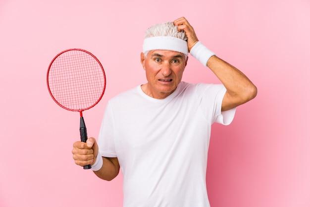 Homem de meia idade jogando badminton isolado sendo chocado, ela lembrou importante reunião. Foto Premium