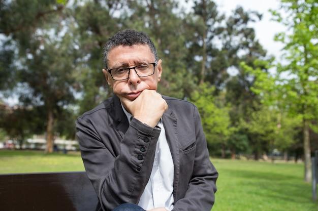 Homem de meia idade pensativo sentado no banco no parque da cidade Foto gratuita