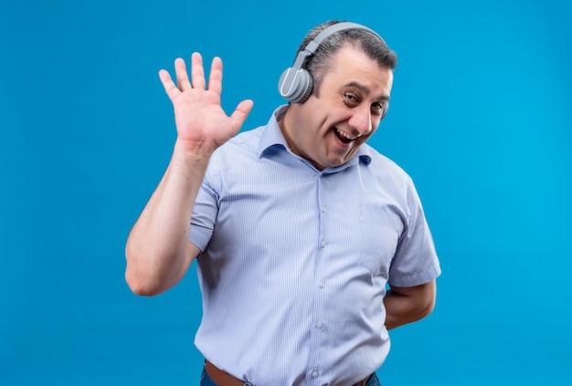 Homem de meia-idade positivo e alegre, com camisa listrada azul e fones de ouvido, mostrando gesto de mais cinco em um fundo azul Foto gratuita