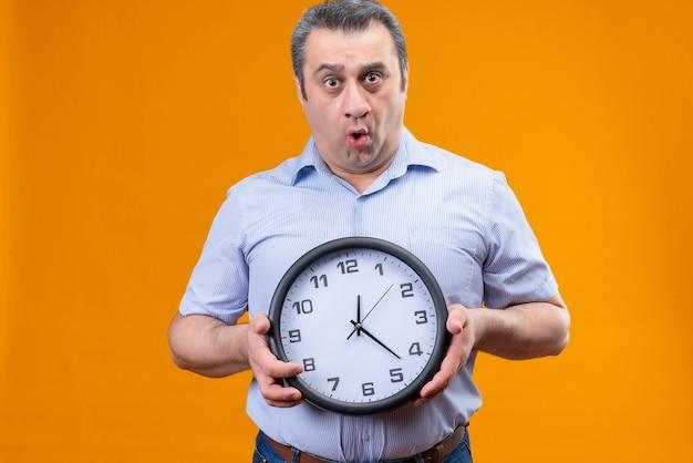 Homem de meia-idade surpreso com uma camisa listrada azul, segurando um relógio de parede em um fundo laranja Foto gratuita