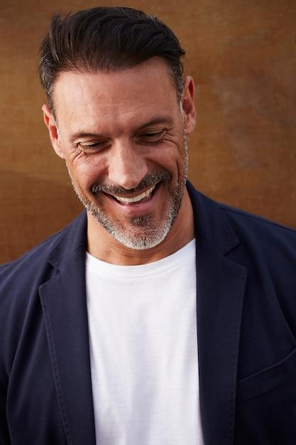 Homem de meia idade, vestindo uma jaqueta rindo feliz Foto gratuita