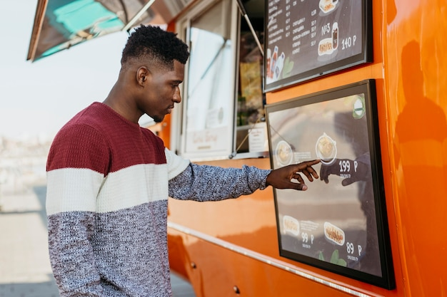 Homem de meio tiro lendo cardápio de food truck Foto gratuita