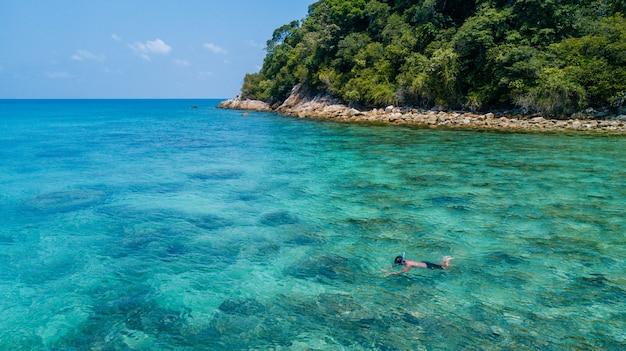Homem de mergulho sozinho em um mar tropical sobre recifes de corais com água cristalina azul clara. ilha perhentian, malásia Foto Premium