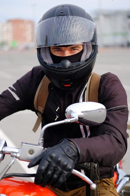 Homem de motociclista ou cara-piloto em um capacete protetor sentado em uma motocicleta. Foto Premium