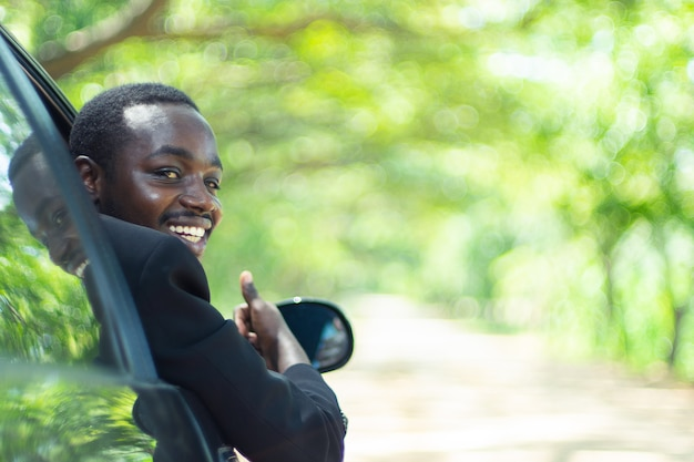 Homem de negócio africano que conduz e que sorri ao sentar-se em um carro com a janela dianteira aberta. Foto Premium