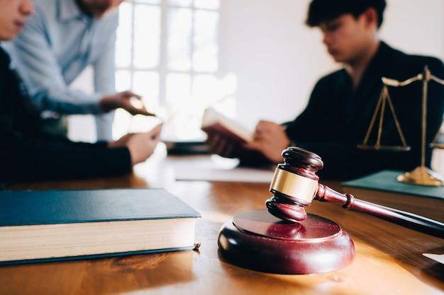 Homem de negócio e equipe e advogados que discutem papéis do contrato com a escala de bronze na mesa de madeira no escritório. lei, serviços jurídicos, conselhos, conceito de justiça. Foto Premium